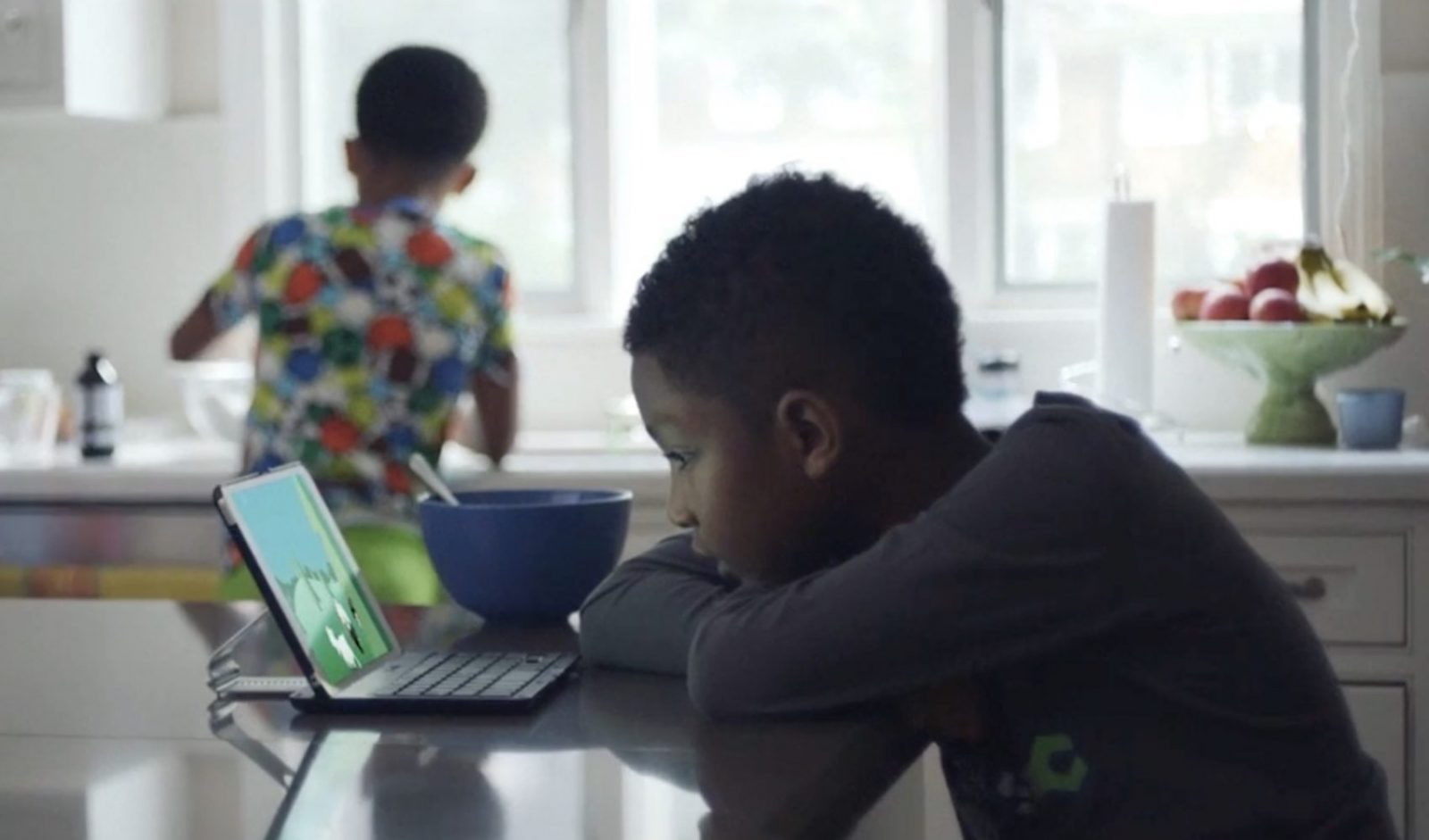 Young boy eating breakfast watching his computer